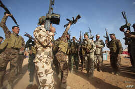 Iraqi fighters from the Shiite Muslim Al-Abbas popular mobilisation unit hold up their weapons in the area surrounding the village of Nukhayb in the embattled Anbar province west of the capital Baghdad, May 19, 2015.
