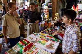 FILE - A bazaar vendor selling patriotic and pro-independence ware talks with a customer in Irbil, Iraq, Aug. 24, 2017. Despite calls from Baghdad and the United States to postpone the vote, Iraq's semiautonomous Kurdish region is pressing ahead with