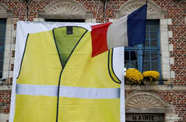 A giant banner showing a yellow vest, as a symbol of French drivers' protest against higher fuel prices, is displayed ahead of a nationwide protest on the facade of the town hall in Morbecque, France, Nov. 15, 2018.