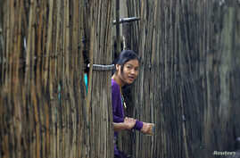 FILE - A refugee who fled Myanmar watches from behind a bamboo wall of a stilt house as Thai authorities conduct a census at Mae La refugee camp, near the Thailand-Myanmar border in Mae Sot district, Tak province, Thailand. Many refugees are hopeful ...