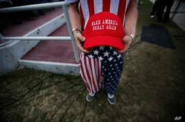 """A man dressed in American flag clothes holds """"Make America Great Again"""" hats before a campaign rally at the Ladd–Peebles Stadium,  Dec. 17, 2016, in Mobile, Alabama. Comedians the world over thrive on slogans and this one has not remained unscathed."""