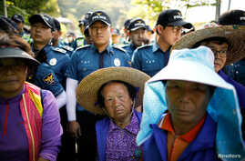 Villagers are blocked by South Korean policemen as they march during an anti-THAAD protest near an entrance of a golf course where a Terminal High Altitude Area Defense (THAAD) system is deployed, in Seongju, South Korea, June 14, 2017.