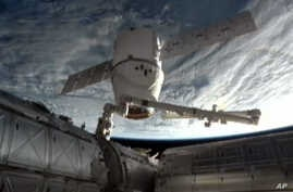 FILE - An image provided by NASA-TV shows the SpaceX Dragon commercial cargo craft as it is backed away from the International Space Station March 26, 2013 by the International Space Station's Canadarm2 robotic arm.