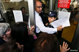 A Laiki Bank manager helps a police officer to enter the bank after getting past depositors waiting for the opening of the bank's branch in Nicosia March 28, 2013.