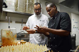 Executive chef Miguel Aguilar (L) shows chef Michael Alejandro Calvo Oviedo of El Atelier restaurant in Havana, Cuba, how to make chicken ropa vieja empanadas at Wynwood Kitchen & Bar in Miami, Florida, Aug. 13, 2015.