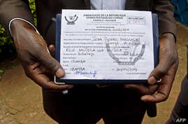 FILE - A member of the defunct M23 rebels holds an embassy form that could decide who is eligible for amnesty.