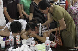 The parents (bottom) of Wang Linjia, one of the two girls killed during the Asiana Airlines plane crash on Saturday, cry at a middle school in Quzhou, Zhejiang province, July 7, 2013. An emergency vehicle rushing to the scene of the Asiana Airlines c