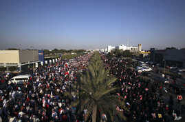 Tens of thousands of Bahraini pro-democracy protesters wave signs and national flags during a march along a divided four-lane highway near Barbar, Bahrain, west of the capital of Manama, Feb. 15, 2014.