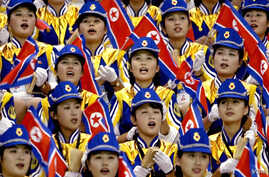 FILE - North Korean women cheer their men's basketball team during a 2002 game at the 14th Asian Games.