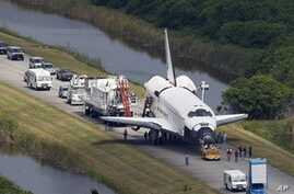 Space shuttle Atlantis is towed to the Orbitor Processing facility for decommissioning at the Kennedy Space Center at Cape Canaveral, Florida, July 21, 2011