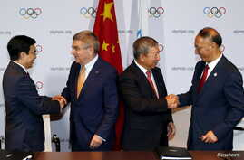 Mayor of Beijing Wang Anshun (L) and President of Chinese OC Committee Liu Peng (R) congratulated by IOC's President Thomas Bach (2nd L) and IOC's Vice President Ng Ser Miang after a signing ceremony in Kuala Lumpur, July 31, 2015.