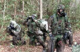 FILE - U.S. Marines take a break during an obstacle course exercise wearing protective chemical, biological gear at Camp Geiger, North Carolina, Nov. 1, 2001.