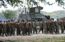 FILE - US marines prepare to board buses outside their temporary base on their way to a nearby air base as the annual US-Philippine joint military exercise winds down at the former US target range in Crow Valley, Capas town, north of Manila on May 15