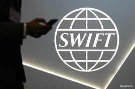 FILE - A man using a mobile phone passes the logo of global secure financial messaging services cooperative SWIFT at the SIBOS banking and financial conference in Toronto, Ontario, Canada