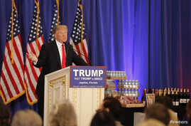 Republican U.S. presidential candidate Donald Trump speaks in front of a display of Trump water, wine and steaks as he talks about the results of the Michigan, Mississippi and other primary elections during a news conference held at his Trump Nationa