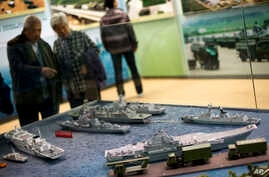 FILE - Visitors look at a scale model of Chinese aircraft carrier Liaoning (bottom right) among the naval ships on display at an exhibition held ahead of the 18th National Congress of the Communist Party of China in Beijing, Nov. 5, 2012.