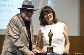 Croatian Auschwitz survivor Branko Lustig and his wife Mirjana stand next to his Academy Award during a ceremony at Yad Vashem Holocaust memorial in Jerusalem, July 22, 2015.