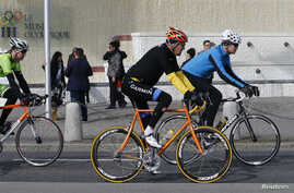 U.S. Secretary of State John Kerry (C) cycles past the Olympic Museum in Lausanne, France, March 16, 2015.