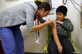 A boy gets an influenza vaccine injection at a health care clinic, in Boston, Massachusetts, January 12, 2013.