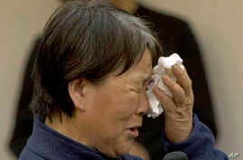 A relative of Chinese passengers onboard the Malaysia Airlines Flight 370, cries as she asks for answers during a meeting with Malaysia embassy and Malaysia Airlines representatives in Beijing, April 21, 2014.