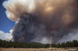 A bulldozer puts in a fire line as the Rim Fire burns in the background near the border of Yosemite National Park, California, Aug. 23, 2013.