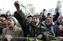 People cheer as they listen to speeches in front of a statue in Independence Square in Kyiv, Feb. 21, 2014.
