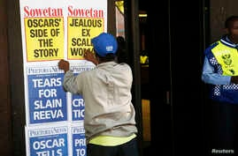 A newspaper vendor puts up posters outside the Pretoria Magistrates court where Oscar Pistorius appeared for a bail hearing, February 20, 2013.