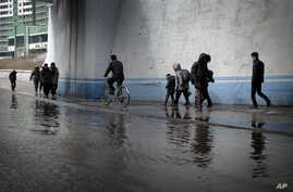 FILE - North Koreans walk along a flooded street.