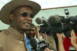 FILE - Former Minister of Information Jonathan Moyo talks to reporters  before voting in Tsholotsho, Zimbabwe. Moyo, who was fired from parliament in November, recently said the international community must help remove the military government that ha