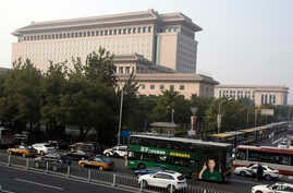 Buses and police vehicles block an area where protesters in green fatigues gather outside the Chinese Ministry of National Defense in Beijing, China, Oct. 11, 2016.