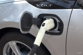 In this image taken from video, an electric vehicle is plugged into a charger, March 2017.