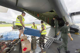 Privates load water bottles and other relief into a French Army logistical transport plane bound for Vanuatu, at the Aerial Military Base Lieutenant Paul Klein (formerly known as La Tontouta), north of Noumea, New Caledonia, on March 15, 2015.