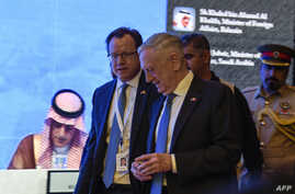 US Defense Secretary James Mattis (C) walks by as Saudi Arabia's Foreign Minister Adel al-Jubeir (L) is seen on a screen addressing the 14th International Institute for Strategic Studies (IISS) Manama Dialogue in the Bahraini capital, Oct. 27, 2018. ...