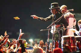 Popular Zimbabwean musician Thomas Mapfumo throws out cds to fans during his performance in Harare, April, 29, 2018, after returning from exile in the United States to perform protest songs in front of tens of thousands of people on the outskirts of
