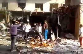 This image made from citizen journalist video posted by the Shaam News Network shows people evacuating a victim of a car bomb attack on a market in the town of Darkoush in Idlib province, Oct. 14, 2013.
