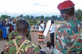 A Sudanese aid worker [C] talks to Sudanese soldiers and scouts on how to spread the message on HIV/AIDS at an internally displaced camp in Juba, southern Sudan, October 2005. (file photo)