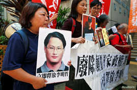 Pro-democracy protesters carry a photo of detained Taiwanese rights activist Lee Ming-Che (L) and other activists during a demonstration in Hong Kong, China, Sept. 11, 2017.