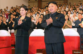 North Korean leader Kim Jong-Un (R) applauds with his wife Ri Sol-Ju (L) during a demonstration performance by the newly formed Moranbong band in Pyongyang in this undated picture released by the KCNA July 9, 2012