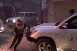 An image grab from a February 8, 2014 Youtube video shows a man running to take cover as U.N. vehicles, one of the World Food Program (R), stopped after a shelling targeted their aid convoy in the besieged districts of Syrian city of Homs.