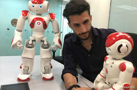 Lucas Apa, senior security consultant at cybersecurity company IOActive, handles robots by UBTech and SoftBank Robotics during a demonstration in Singapore, Aug. 21, 2017.