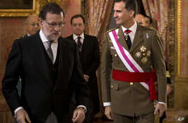 FILE - Spain's King Felipe VI walks with Spain's Prime Minister Mariano Rajoy, left, during the annual Pascua Militar Epiphany ceremony at the Royal Palace in Madrid, Spain, Jan. 6, 2016 file photo. Spain's king is meeting Tuesday with the country's