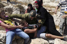 FILE - In this Aug, 28, 2015 photo, Palestinian women and girls scuffle with an Israeli soldier trying to arrest a 12-year-old boy during a protest near the West Bank village of Nebi Saleh.