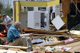 Charles Milam takes a break while searching his destroyed home on Clayton Avenue in Tupelo, Mississippi, April 29, 2014. Milam, his wife and his granddaughter were at home at the time of the tornado, and all survived.