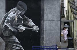 FILE - A woman takes out her rubbish beside a mural depicting a British soldier knocking down the door of a house with a sledge hammer in Derry, Northern Ireland, March 23, 2010.