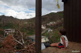 A boy looks at his neighbourhood after Hurricane Maria destroyed the town's bridge and the surrounding areas, in San Lorenzo, Morovis, Puerto Rico, Oct. 5, 2017.