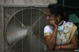 FILE - An Indian women stands in front of an air cooler to cool herself on a hot summer day in Hyderabad, in the southern Indian state of Telangana.