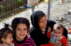 Migrant women cradle children near a fence in a makeshift encampment at Greece's northern border town of Idomeni, March 4, 2016.