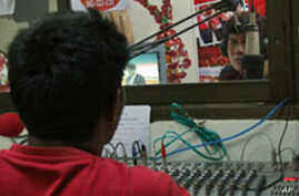 An announcer and a technician inside the studio of 'We Love Udon,' a  'Red Shirt' radio station in Udon Thani, Thailand