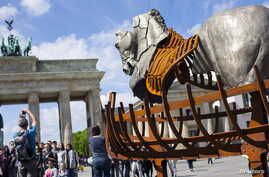 "A man takes a picture near a piece of a traveling art exhibition called ""Lapidarium, Waiting for the Barbarians"" by Mexican artist Gustavo Aceves, in front of Brandenburg Gate in Berlin, Germany, May 4, 2015."