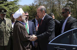 In this photo released by the official website of the office of the Iranian Presidency, Iran's President Hassan Rouhani, left, shakes hand with his Turkish counterpart Recep Tayyip Erdogan during a welcoming ceremony for him at the Saadabad palace in